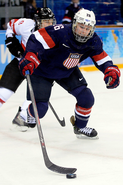 . Kendall Coyne (26) of the U.S.A. controls the puck as Stefanie Marty (9) of the Switzerland defends during the second period of action at the Shayba Arena on Monday, February 10, 2014. (Photo by AAron Ontiveroz/The Denver Post)