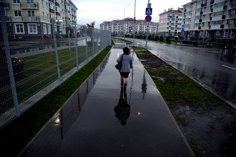 . A woman walks in the rain near a series of hotels. Sochi 2014 Winter Olympics on Tuesday, February 18, 2014. (Photo by AAron Ontiveroz/The Denver Post)