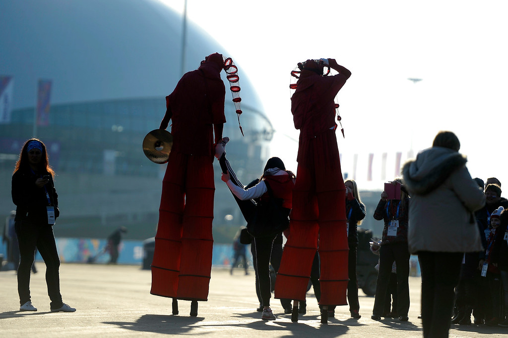 . A pair of stilted street performers help a young woman stretch during opening weekend at the Olympic village on Saturday, February 8, 2014. (Photo by AAron Ontiveroz/The Denver Post)