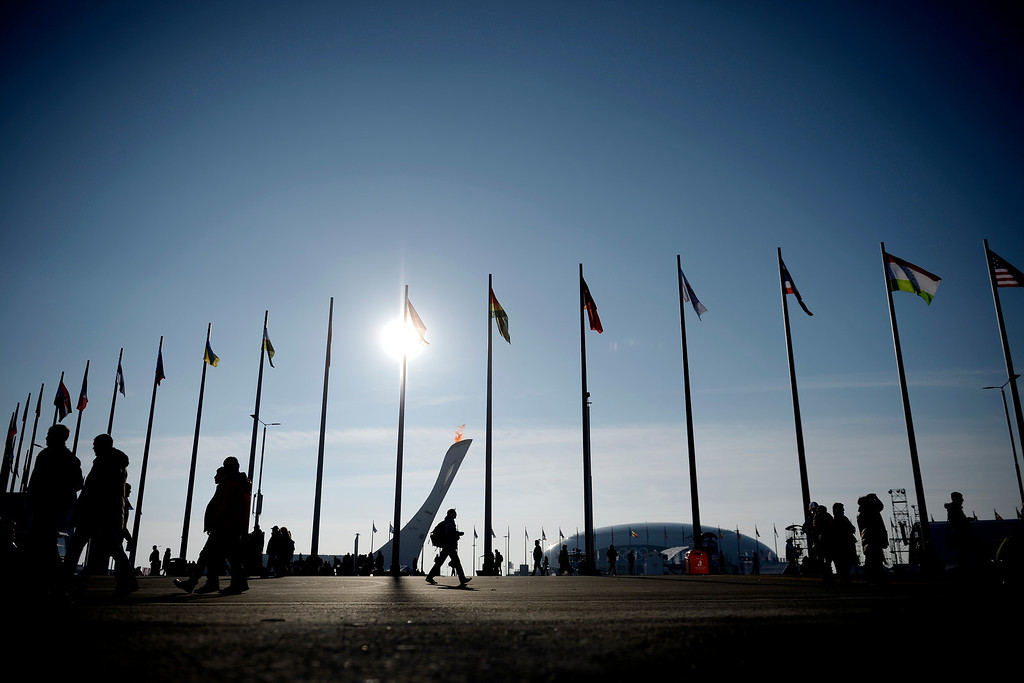 . People walk beneath the national flags of teams competing as the Olympic Torch burns during opening weekend at the Olympic village during the Sochi 2014 Winter Olympics on Saturday, February 8, 2014. (Photo by AAron Ontiveroz/The Denver Post)