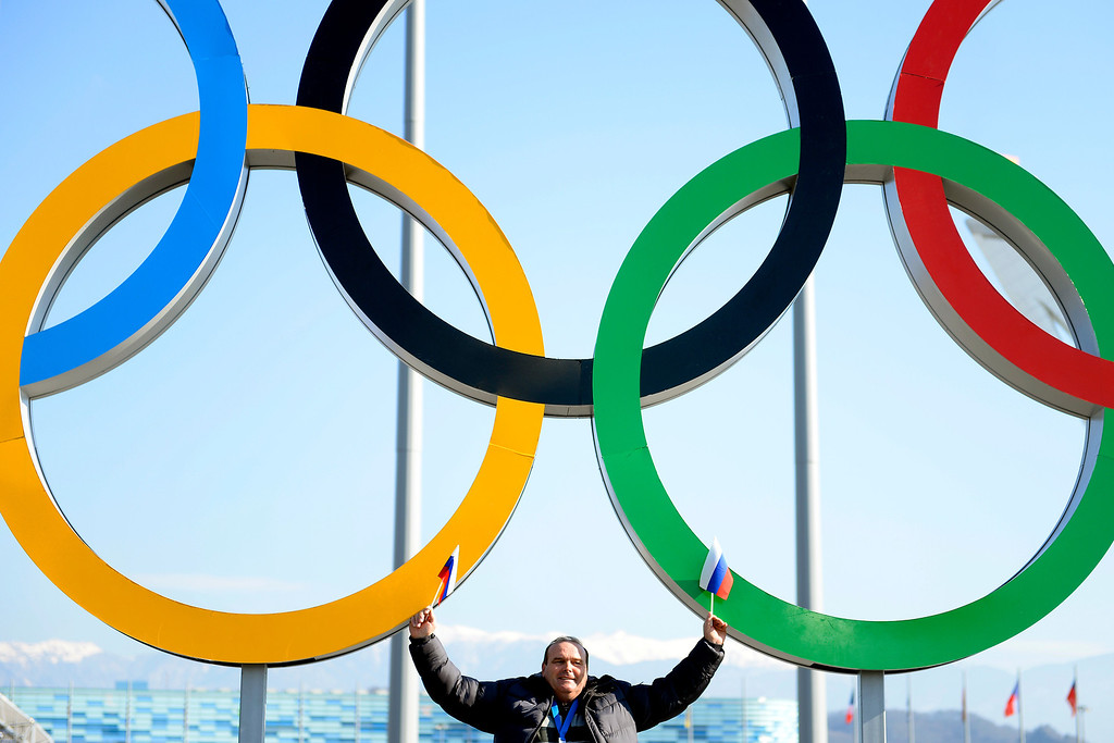 . A Russian man holds two flags as he poses for a photo in the Olympic village on the first weekend of the games on Saturday, February 8, 2014. (Photo by AAron Ontiveroz/The Denver Post)