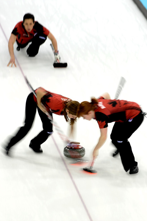 . Canada\'s Jill Officer watches as teammates Kaitlyn Lawes (left) and Dawn McEwen sweep during a women\'s curling qualifier against Great Britain at the Ice Cube Curling Center. Sochi 2014 Winter Olympics on Wednesday, February 12, 2014. (Photo by AAron Ontiveroz/The Denver Post)