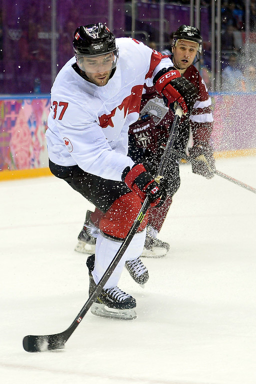 . Patrice Bergeron (37) of the Canada takes a shot against Latvia during the third period of Canada\'s 2-1 win over Latvia. Sochi 2014 Winter Olympics on Wednesday, February 19, 2014 at Bolshoy Ice Arena. (Photo by AAron Ontiveroz/ The Denver Post)