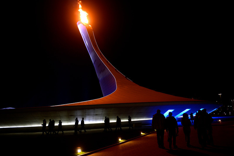 . The Olympic Torch burns brightly into the night as people visit the Sochi 2014 village. Sochi 2014 Winter Olympics on Friday, February 14, 2014. (Photo by AAron Ontiveroz/The Denver Post)