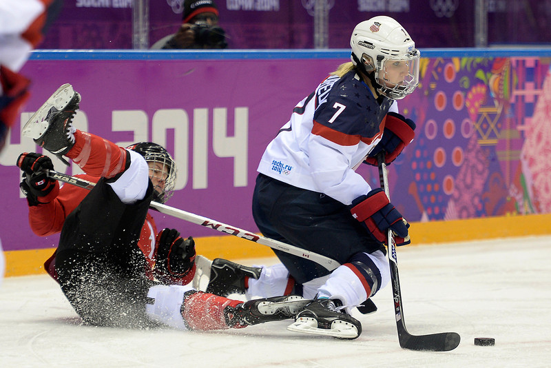. Catherine Ward (18) of the Canada falls to the ice as Monique Lamoureaux (7) of the U.S.A. controls the puck during the second period of the women\'s gold medal ice hockey game. Sochi 2014 Winter Olympics on Thursday, February 20, 2014 at Bolshoy Ice Arena. (Photo by AAron Ontiveroz/ The Denver Post)