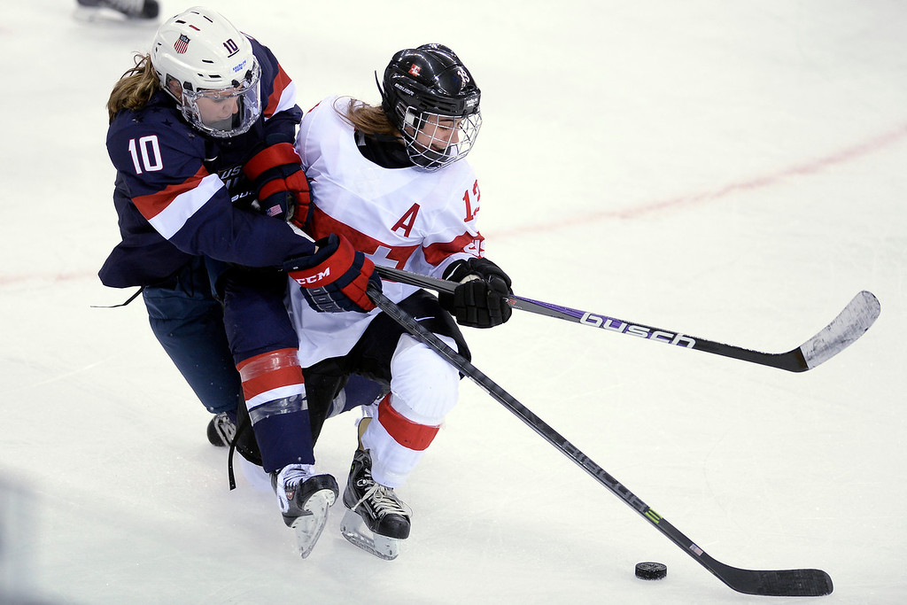. Sara Benz (13) of the Switzerland and Meghan Duggan (10) of the U.S.A. tangle as they vie of the puck during the third period of the United States\' 9-0 win at the Shayba Arena on Monday, February 10, 2014. (Photo by AAron Ontiveroz/The Denver Post)