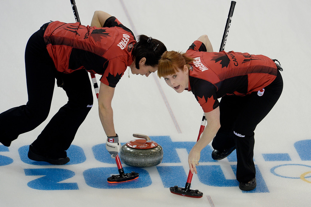 . Canadian curlers Jill Officer (left) and Dawn McEwen sweep the ice ahead of the stone during a women\'s curling qualifier against Great Britain at the Ice Cube Curling Center. (Photo by AAron Ontiveroz/The Denver Post)