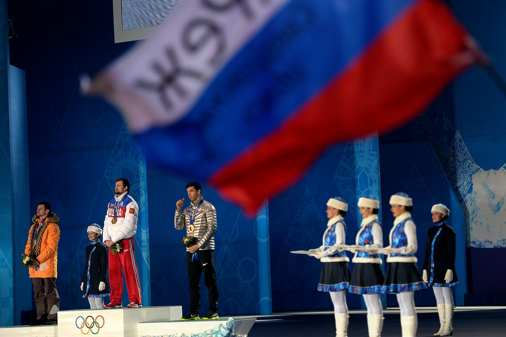 . A fan waves a flag as gold medalist Alexander Tretiakov of Russia stands on the podium with silver medalist Martins Dukurs of Latvia (right) and bronze medalist Matthew Antoine watch the presentation during the medals ceremony for the men\'s skeleton.   (Photo by AAron Ontiveroz/The Denver Post)