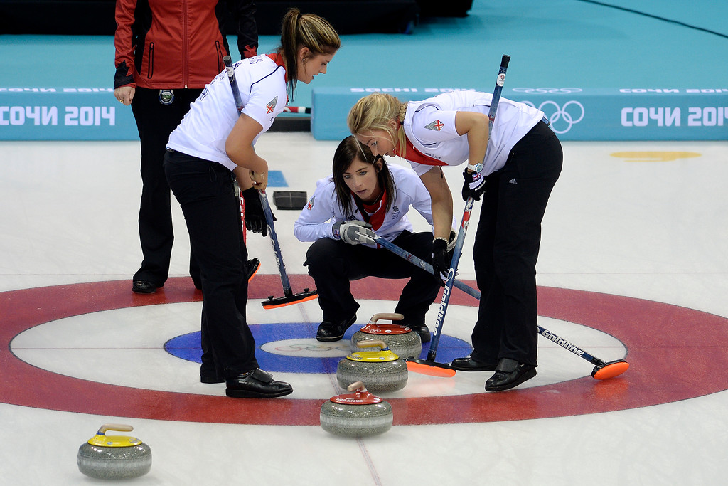 . Great Britain skip Eve Muirhead watches as the third Anna Sloan sweeps and the second Vicki Adams looks on during a women\'s curling qualifier against Canada at the Ice Cube Curling Center on Wednesday, February 12, 2014. (Photo by AAron Ontiveroz/The Denver Post)