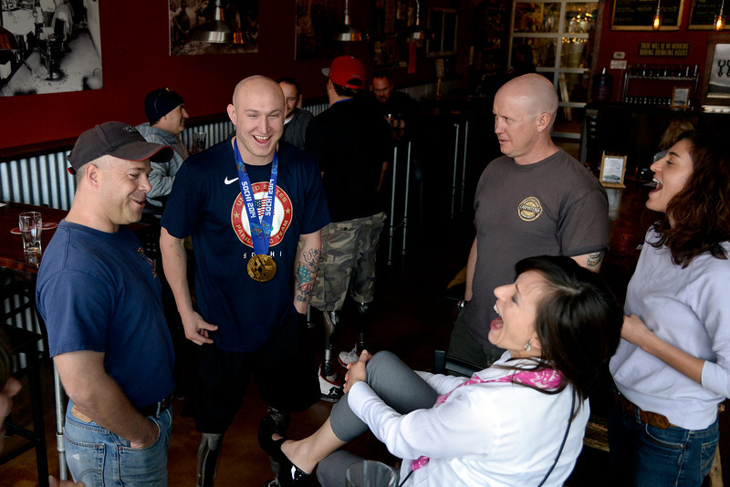. U.S.A. Paralympics sled hockey gold medalist Tyler Carron (with medal) jokes with patrons at City Star Brewing, Berthoud, Colorado on Thursday, March 20, 2014. (Photo by AAron Ontiveroz/The Denver Post)