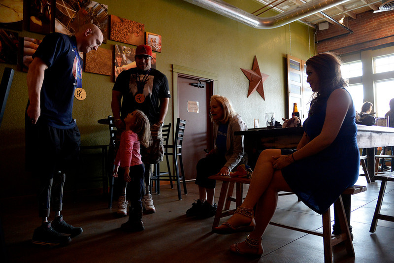 ". Zuri Bernal, 5, speaks with U.S.A. Paralympics sled hockey team members Tyler Carron (left) and Nikko Landeros at City Star Brewing in Berthoud, Colorado on Thursday, March 20, 2014. Bernal asked, ""Are you robots?\"" To which Carron smiled and replied, \""We are partially bionic.\"" (Photo by AAron Ontiveroz/The Denver Post)"