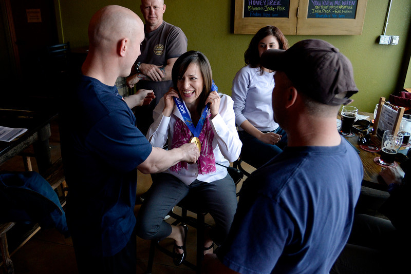 . Kristy Hall laughs as she tries on U.S.A. Paralympics sled hockey gold medalists Tyler Carron\'s Olympic hardware as he and teammate Nikko Landeros (not pictured) visit their hometown, Berthoud, Colorado on Thursday, March 20, 2014.  (Photo by AAron Ontiveroz/The Denver Post)