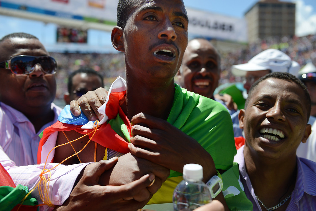 . Fans run onto Folsom Field on the University of Colorado campus to celebrate with Afewerki Berhane, of Eritrea, who was the first male finisher in the international team race at the 36th Annual BolderBOULDER 10K road race on Memorial Day, May 26, 2014.  (Photo By Lindsay Pierce/The Denver Post)