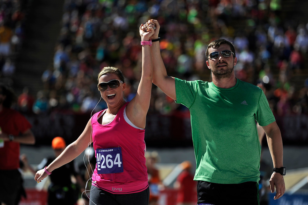 . Jayme Holcombe and Michael Holcombe, of Castle Rock, hold hands as they cross the finish line of the 36th Annual Bolder Boulder 10K road race at Folsom Field on the University of Colorado campus, Memorial Day, May 26, 2014. (Photo By Lindsay Pierce/The Denver Post)
