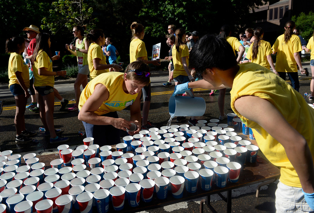 . Volunteers fill cups with water for the runners along Walnut Street. The 36th BolderBoulder takes place on the streets of Boulder, CO on Memorial Day, May 26, 2014. The 10K event brings winds through the streets of Boulder and finishes at Folsom Field on the University of Colorado campus. (Kathryn Scott Osler, The Denver Post)