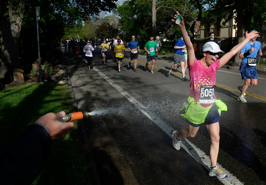 . Rachel Doriese from Boulder gets a cool shot of water from a hose held by Adam Massey. The 36th BolderBoulder takes place on the streets of Boulder, CO on Memorial Day, May 26, 2014. The 10K event brings winds through the streets of Boulder and finishes at Folsom Field on the University of Colorado campus. (Kathryn Scott Osler, The Denver Post)