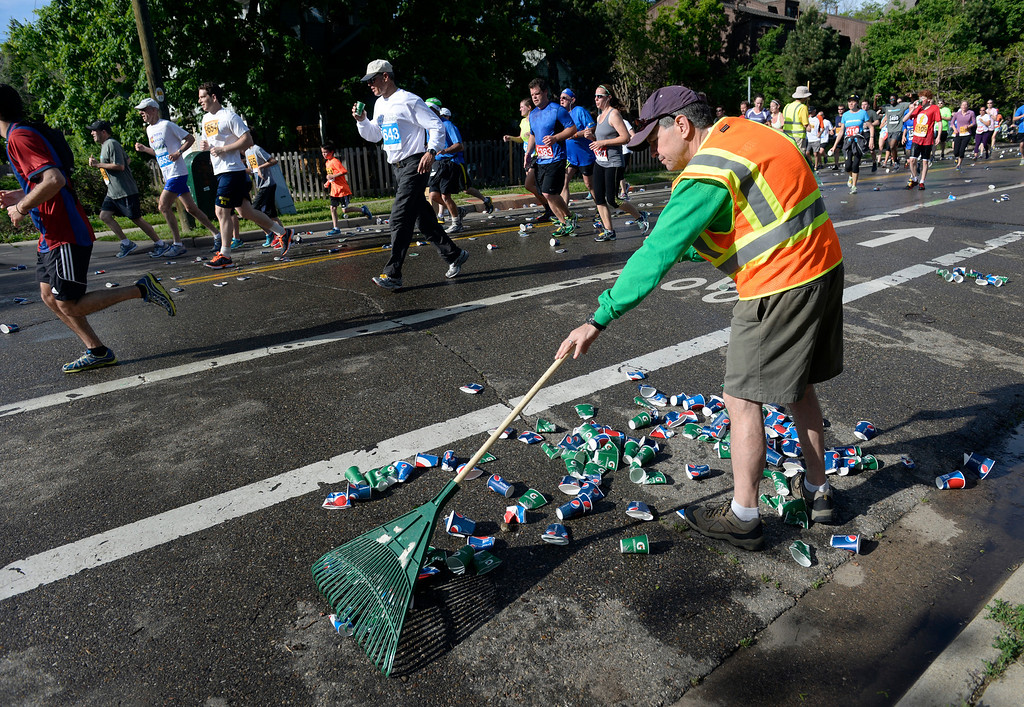. As runners make their way down Walnut Street, volunteer Don Boselli uses a rake to clean up the used paper drinking cups. The 36th BolderBoulder takes place on the streets of Boulder, CO on Memorial Day, May 26, 2014. The 10K event brings winds through the streets of Boulder and finishes at Folsom Field on the University of Colorado campus. (Kathryn Scott Osler, The Denver Post)