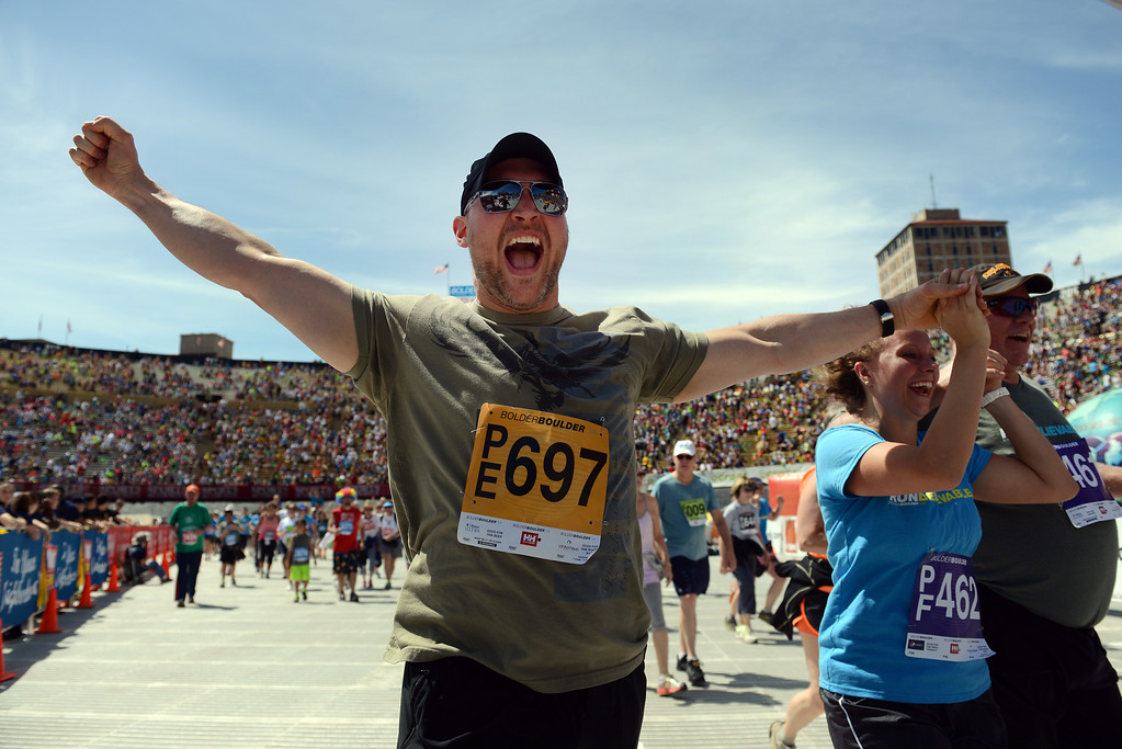 . Ryan Landis, left, of Arvada, celebrates, while holding Ilsa Hale\'s hand as they cross the finish line of the 36th Annual BolderBOULDER 10K road race on Folsom Field at the University of Colorado campus, Memorial Day, May 26, 2014.  (Photo By Lindsay Pierce/The Denver Post)