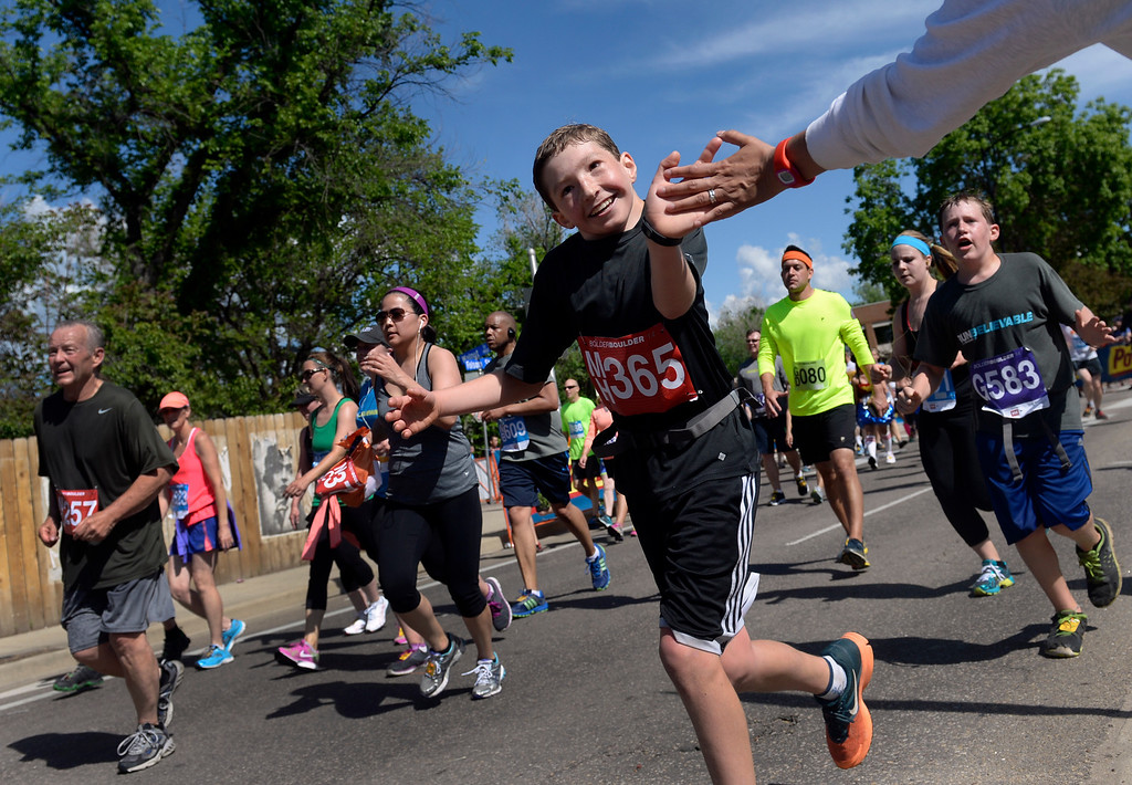 . Adriana Garcia, right, gives a cheer and a high-five to runners including Dylan Carey of Denver. The 36th BolderBoulder takes place on the streets of Boulder, CO on Memorial Day, May 26, 2014. The 10K event brings winds through the streets of Boulder and finishes at Folsom Field on the University of Colorado campus. (Kathryn Scott Osler, The Denver Post)