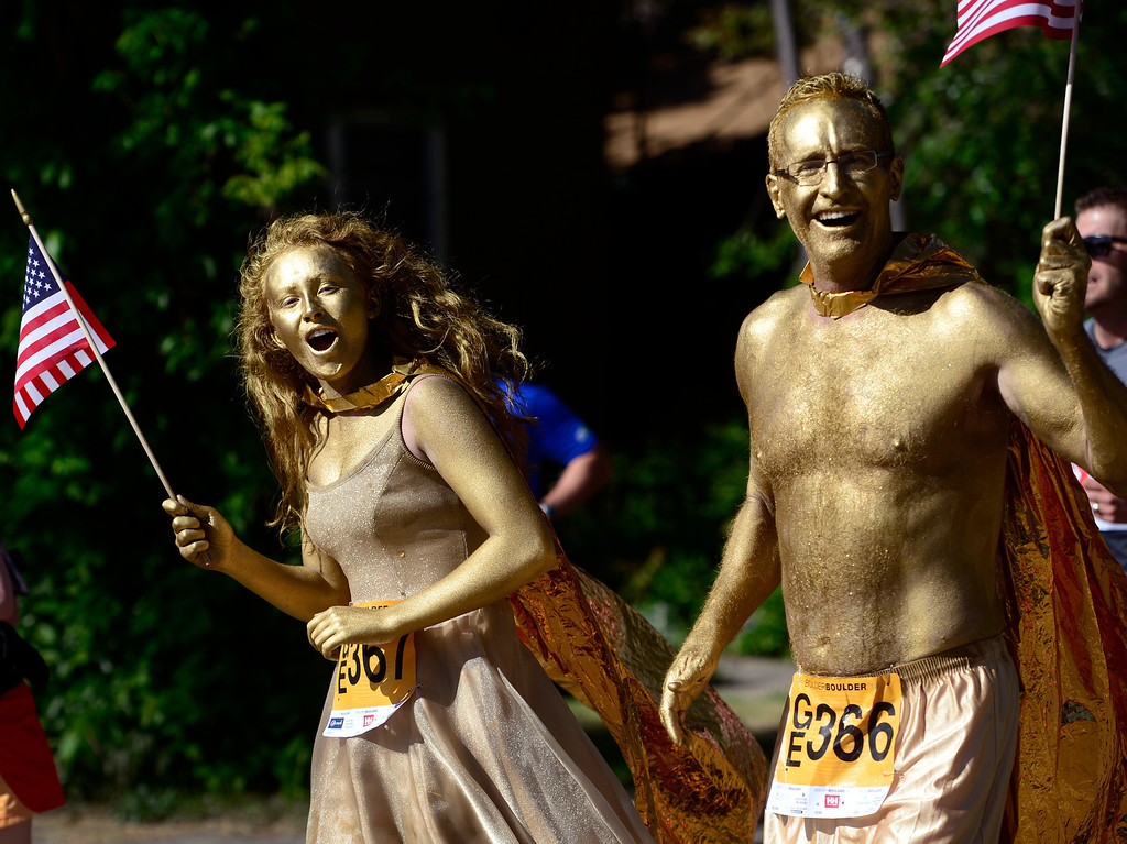 . Peter, right, and Kelly Dinneen from Littleton, dressed in gold for the occasion. The 36th BolderBoulder takes place on the streets of Boulder, CO on Memorial Day, May 26, 2014. The 10K event brings winds through the streets of Boulder and finishes at Folsom Field on the University of Colorado campus. (Kathryn Scott Osler, The Denver Post)