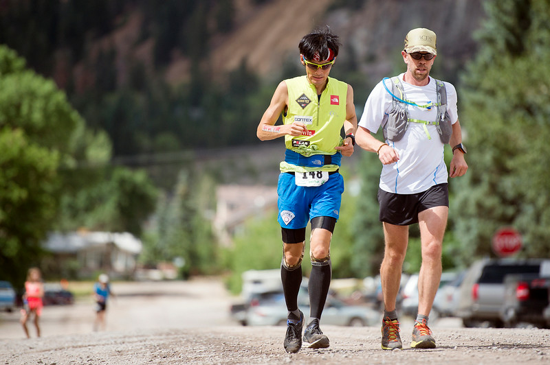 . Tsuyoshi Kaburaki #148 races near mile 44 with an unidentified pacer, right, just after the aid station in Ouray on 2nd Avenue during the 100.5-mile Hardrock 100 Endurance Run on July 11, 2014, in the San Juan Mountains in Ouray, Colorado. (Photo by Daniel Petty/The Denver Post)