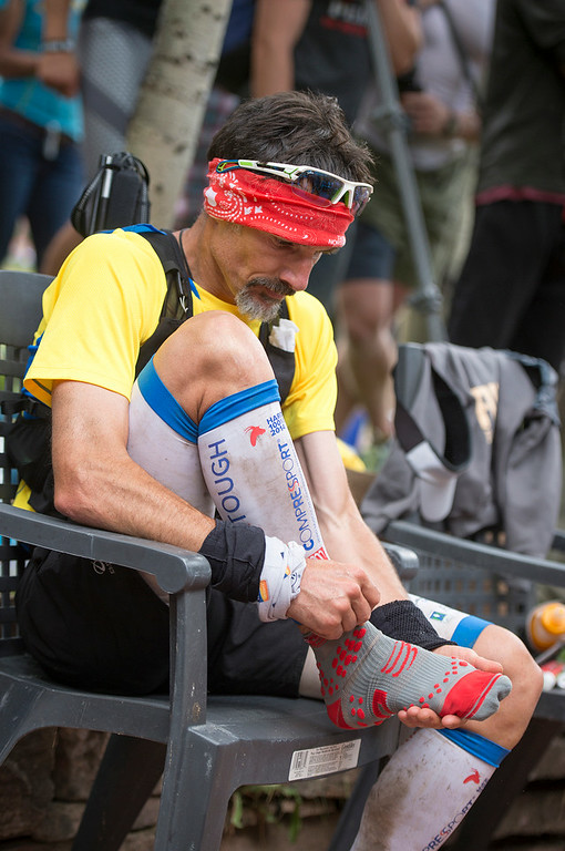 . Sebastien Chaigneau #1 of France changes his shoes and socks at the Telluride Aid Station in Town Park near mile 28 of the the 100.5-mile Hardrock 100 Endurance Run on July 11, 2014, in the San Juan Mountains in Telluride, Colorado. Chaigneau won the 100.5-mile race in 2013. (Photo by Daniel Petty/The Denver Post)