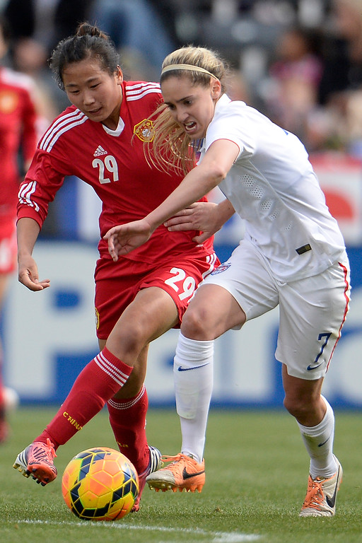 . Morgan Brian (7) of the U.S.A. and Yang Li (29) of China compete for the ball during the first half of women\'s soccer action. Dick\'s Sporting Goods Park on Sunday, April 6, 2014. (Photo by AAron Ontiveroz/The Denver Post)