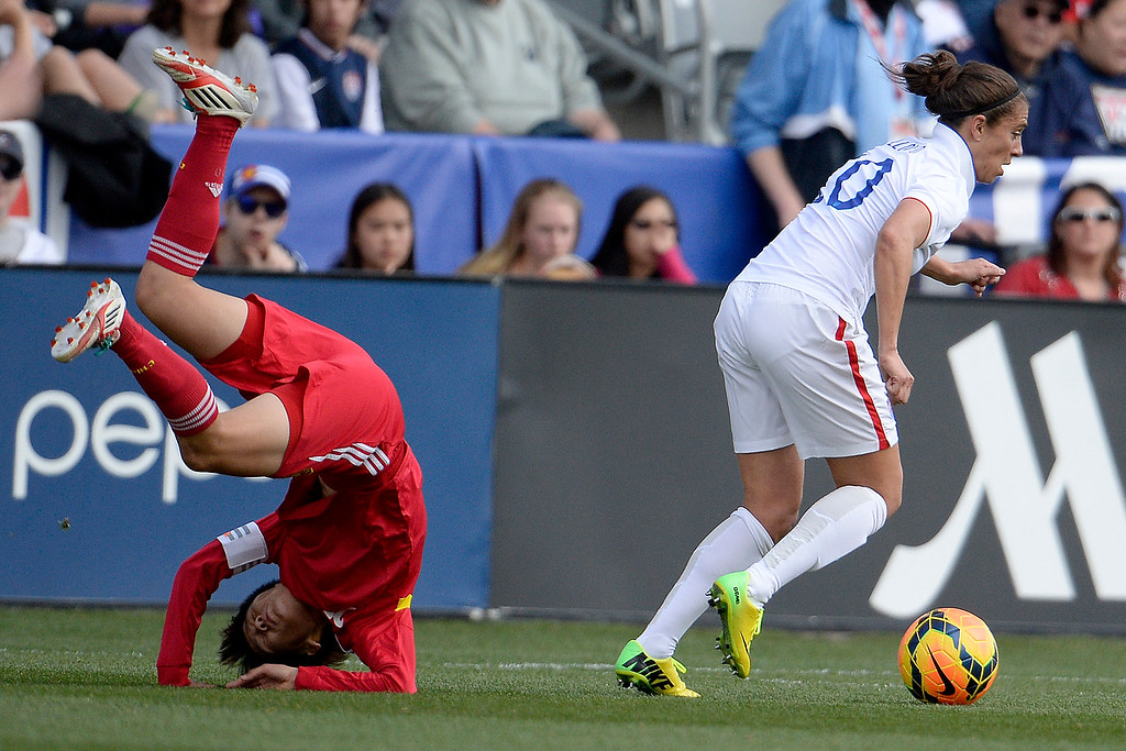 . Carli Lloyd (10) of the U.S.A. controls the ball as Zhang Rui (25) of China topples during the first half of women\'s soccer action. Dick\'s Sporting Goods Park on Sunday, April 6, 2014. (Photo by AAron Ontiveroz/The Denver Post)