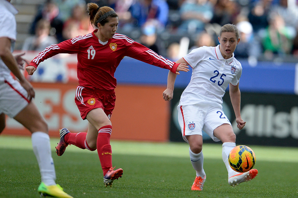 . Megan Klingenberg (25) of the U.S.A. kicks the ball away from Zhou Feifei (19) of China during the second half of the U.S.A.\'s 2-0 win. Dick\'s Sporting Goods Park on Sunday, April 6, 2014. (Photo by AAron Ontiveroz/The Denver Post)