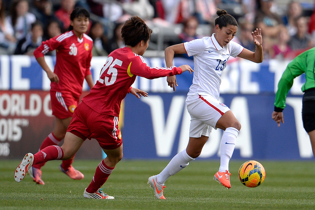 . Christen Press (23) of the U.S.A. dribbles the ball as Zhang Rui (25) of China defends during the first half of women\'s soccer action. Dick\'s Sporting Goods Park on Sunday, April 6, 2014. (Photo by AAron Ontiveroz/The Denver Post)