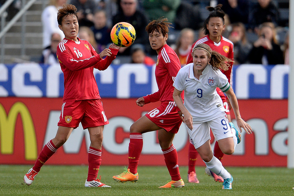 . Heather O�Reilly (9) of the U.S.A. races the ball against Wang Chen (16) of China and Han Peng (18) during the first half of women\'s soccer action. Dick\'s Sporting Goods Park on Sunday, April 6, 2014. (Photo by AAron Ontiveroz/The Denver Post)