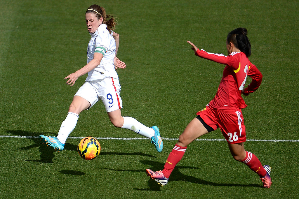 . Heather O�Reilly (9) of the U.S.A. passes the ball as Li Dongna (26) of China defends during the second half of the U.S.A.\'s 2-0 win. Dick\'s Sporting Goods Park on Sunday, April 6, 2014. (Photo by AAron Ontiveroz/The Denver Post)