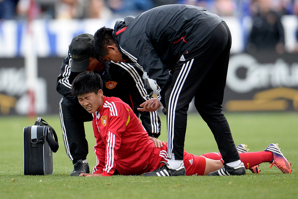 . Ren Guixin (23) of China grimaces on the turf after taking contact against the U.S.A. during the first half of women\'s soccer action. Dick\'s Sporting Goods Park on Sunday, April 6, 2014. (Photo by AAron Ontiveroz/The Denver Post)