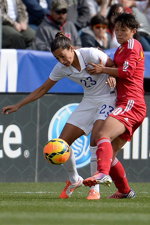 . Liu Shanshan (30) of China and Christen Press (23) of the U.S.A. tangle during the first half of women\'s soccer action. Dick\'s Sporting Goods Park on Sunday, April 6, 2014. (Photo by AAron Ontiveroz/The Denver Post)