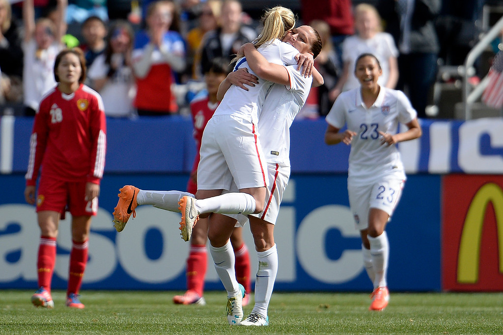 . Lauren Holiday (12) celebrates her 1-0 goal against China as teammate Morgan Brian (7) jumps into her arms during the first half of women\'s soccer action. Dick\'s Sporting Goods Park on Sunday, April 6, 2014. (Photo by AAron Ontiveroz/The Denver Post)