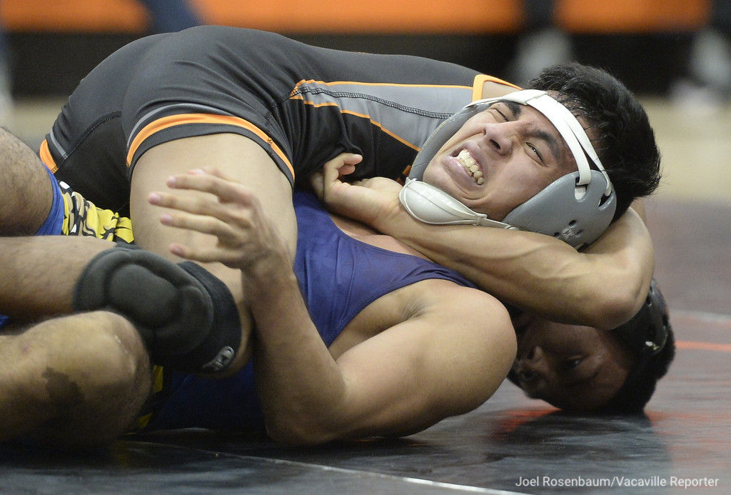. Vaca High�s Jacob Peralta battles Wood�s Alex Rivera during their 128 pound match during the Bulldogs duel meet against the Wildcats. Peralta won by major decision and the �Dogs won the meet 62-6.