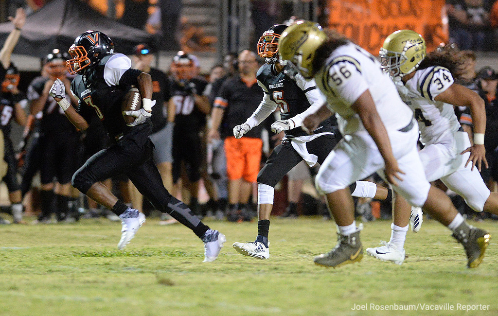. Vaca High�s Nick Smith sprints away from Burbank High�s Taniela Samate (56) and Duke-Washington Finau (34) for a touchdown during a punt return during the Bulldogs� 40-14 victory over the Titans Friday in their home opener at Tom Zunino Stadium.