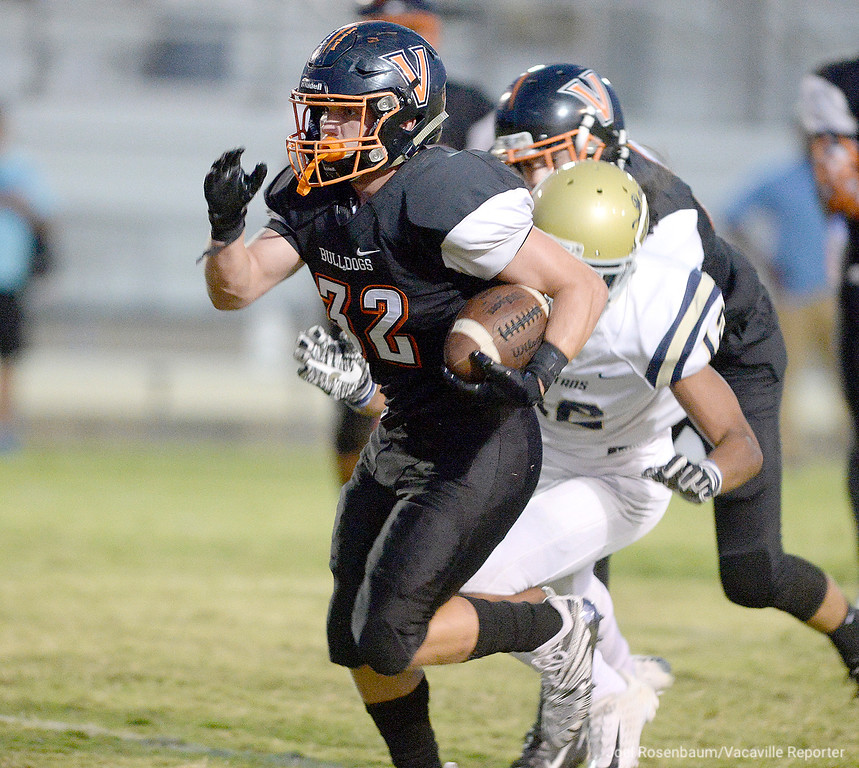 . Vaca High running back, Talon Abramowicz sprints away from the pressure from Burbank High\' free safety, Edward Asi during the first quarter.