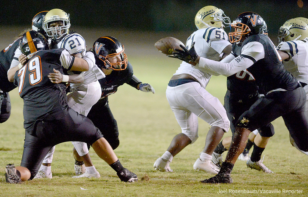 . Vacaville High defensive end, Michael Brown (right) catches a fumble from Burbank High\'s Darius Daniel (21) out the air during the second quarter of the Bulldogs\' 40-14 rout Friday at Tom Zunino Stadium.