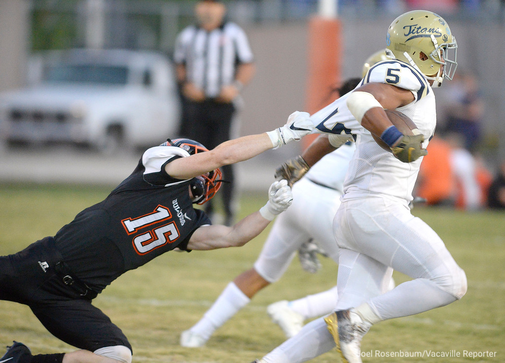 . Vaca High\'s Devon Mills grabs a handful of jersey as he attempts to tackle Burbank High\'s Taniela Fisilau during the first quarter.
