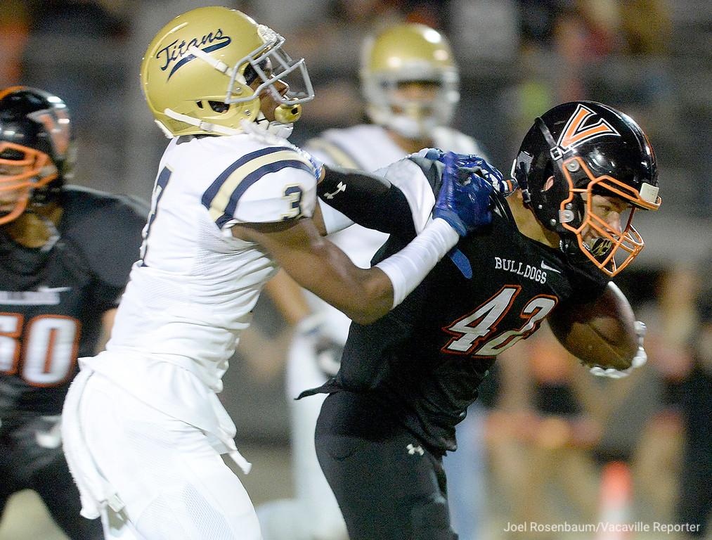 . Vaca High running back, Clayton Watterson stiff-arms Burbank High\'s Quincy Wright III as he breaks his tackle while running for a big game in the first quarter of the Bulldogs 40-14 victory Friday at Tom Zunino Stadium.