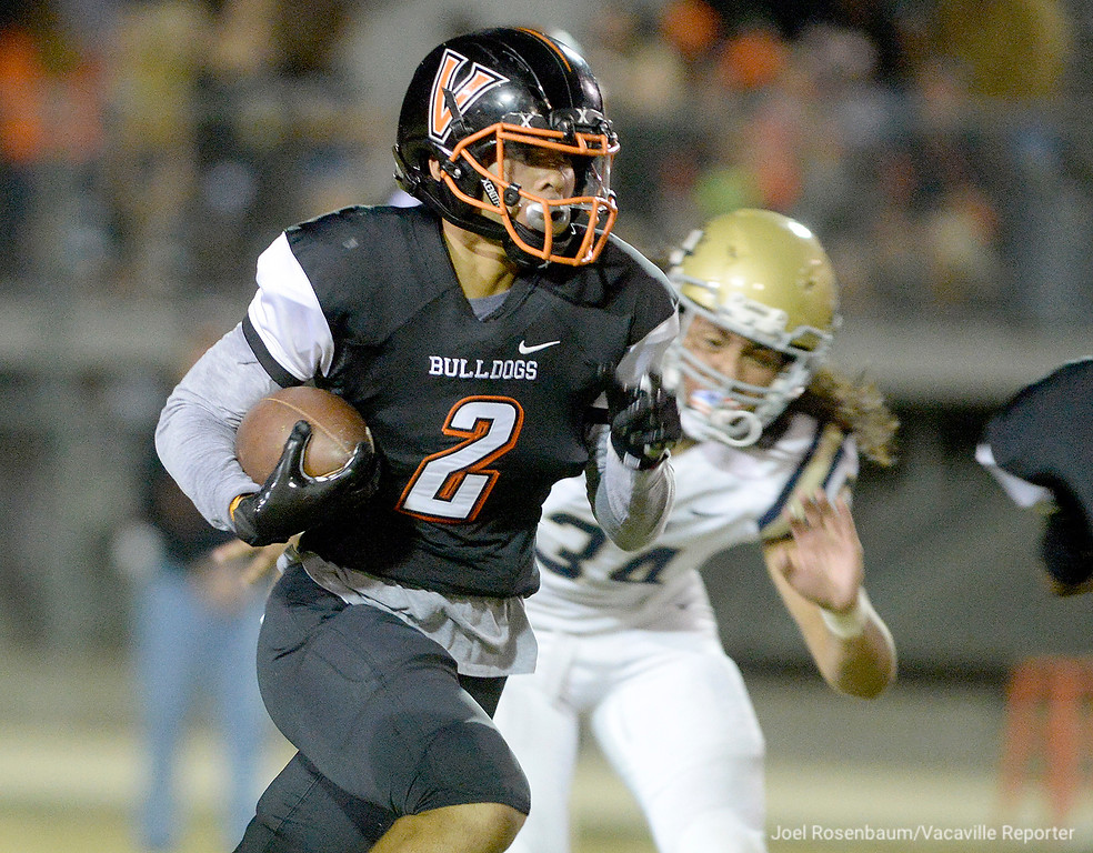 . Vaca High running back, Dylan Warfield sprints away from the pressure from Burbank High\'s Duke-Washington Finau during the first quarter.