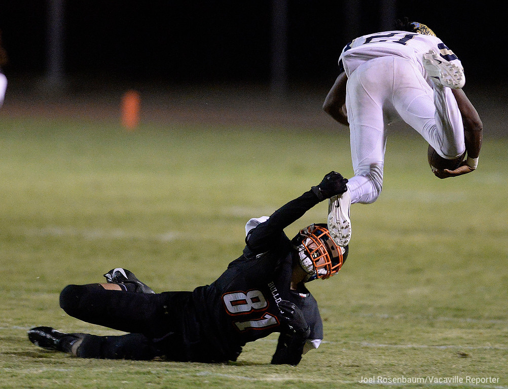 . Vacaville High�s Trevor Marshall trips up Burbank High�s Darius Daniel for a touchdown saving take on kickoff during the second quarter of the Bulldogs� 40-14 rout over the Titans in the home opener Friday at Tom Zunino Stadium.
