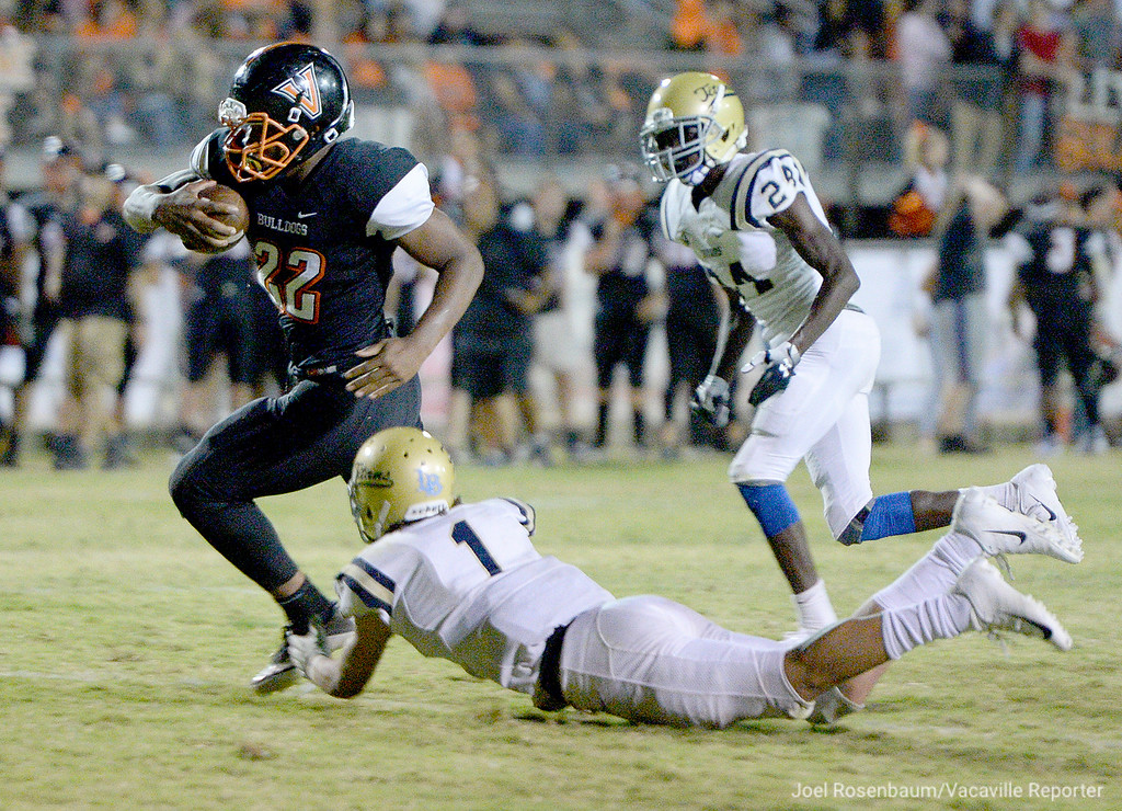 . Vaca High running back, Chris Island runs through the ankle tackle of Burbank High School\'s Lavelle Bailey during a second quarter touchdown. Island rushed for 47 yard on just seven carries in the game.