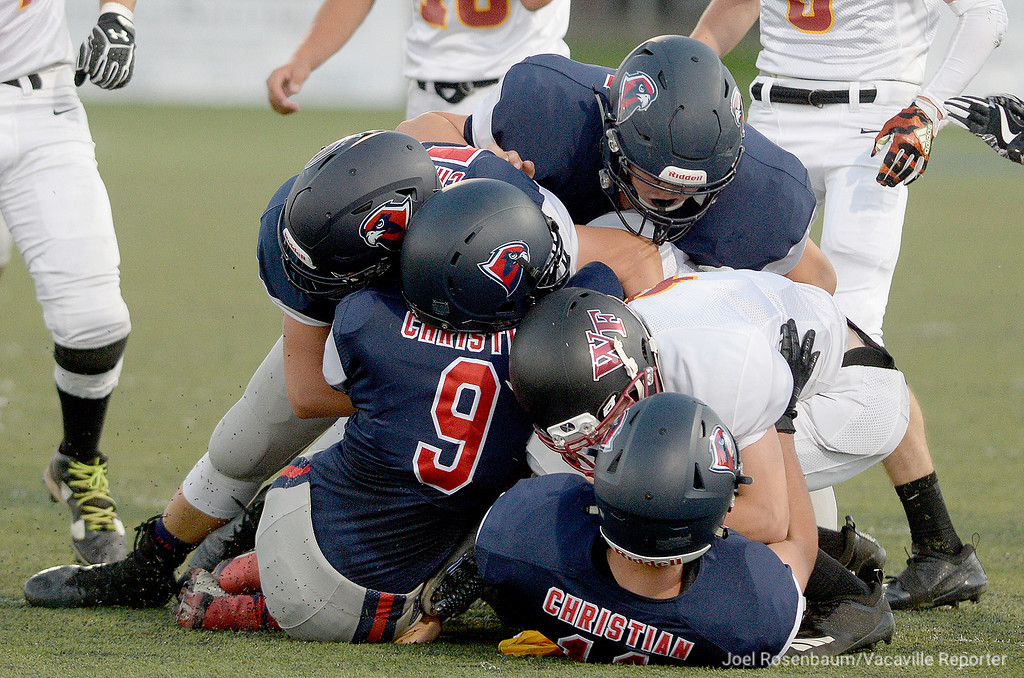 . A host of Vacaville Christian High defenders smother Foresthill High School quarterback, Kaiden Pennington behind the line of scrimmage during the first quarter.