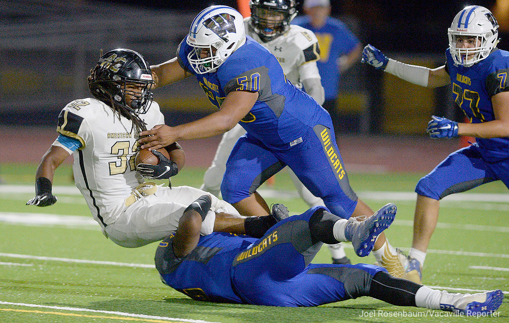 . Will C. Wood defensive linemen  Kamani Currie (bottom) and Javier Contreras stuff American Canyon running back, Eddie Byrdsong for a loss during the fourth quarter of the Wildcats 28-22 victory over the Wolves Friday at Wood.
