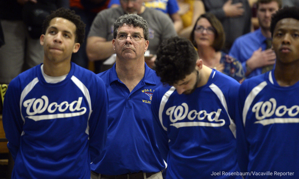 . Will C. Wood High head coach Mark Wudel (second from left) stands with his players as the national anthem is played before tip off of their showdown with their rivals, Vaca High Thursday at Wood.