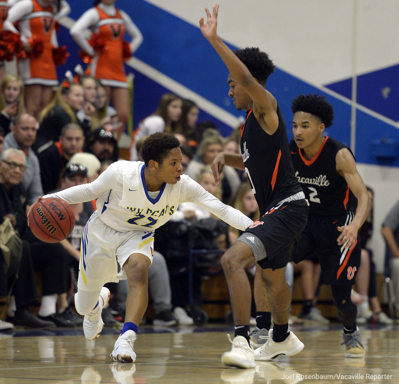 . Will C. Wood\'s Jeremiah Jones looks for an open teammate to pass too around the double team of Vaca High\'s Jordan Adams (middle) and Johnathan Tubbs during the second quarter of the Wildcats\' 59-57 loss to the rival Bulldogs.