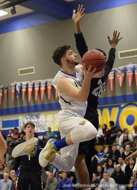 . Will C. Wood\'s Michael Wudel drive past Vaca High\'s CJ Toler during the third quarter. Wudel finished the game with 11 points in the WIldcats\' 59-57 loss.