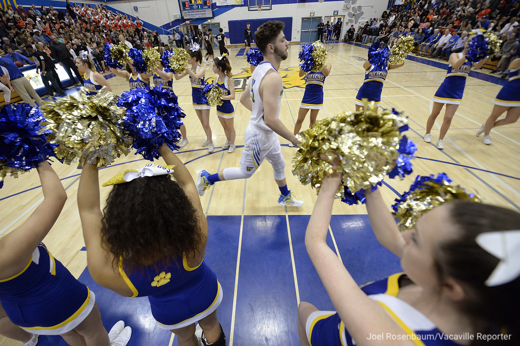 . WIll C. Wood guard, Michael Wudel runs past a line of cheerleaders as he is introduced before tip off with their crosstown showdown with Vaca High.